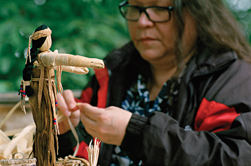 Elizabeth Doxtater works on a cornhusk doll.