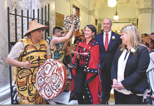 Melanie Mark escorted by B.C. NDP leader, John Horgan, during a swearing in ceremony at legislature as members of the Nisga'a First Nations drummers perform honour song.