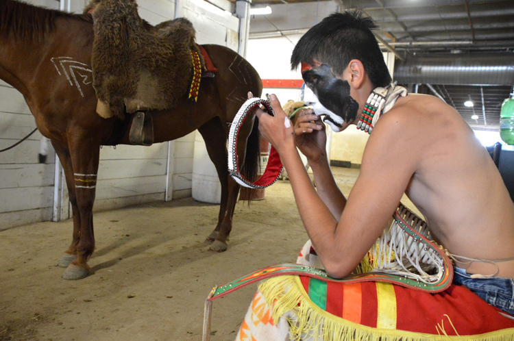 Young Treaty Seven Warrior applying paint.