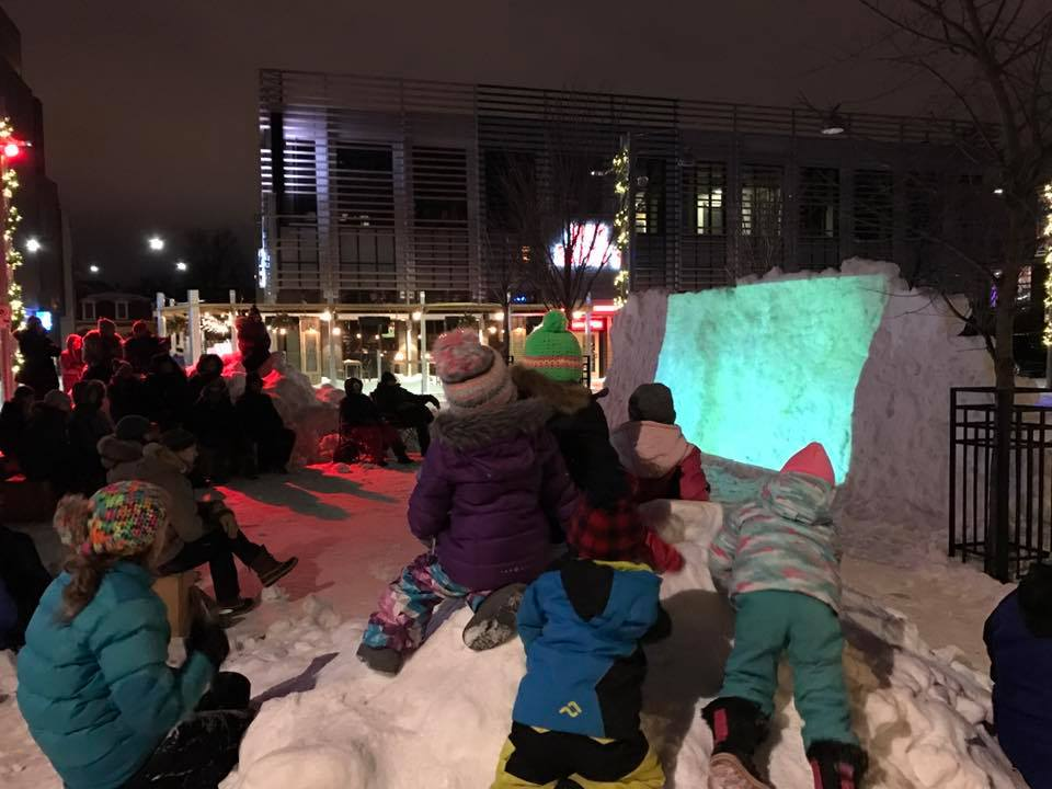 Children watching a film on a screen made of snow.